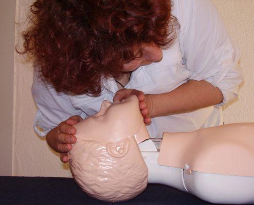 Frau bei Mund-zu-Mund-Beatmung an Puppe