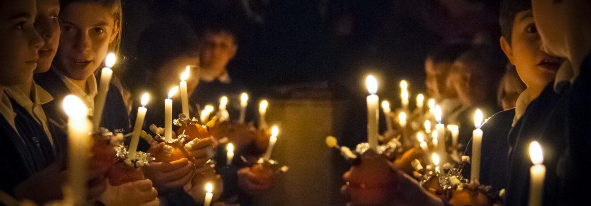 Kinder mit Kerzen in dunkler Kirche